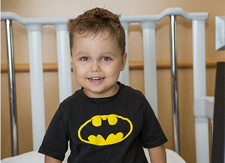 Zaccari laying in a hospital bed with a batman t-shirt on and a smile on his face