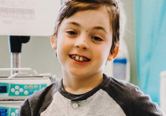 A young boy in a hospital bed smiling at the camera.