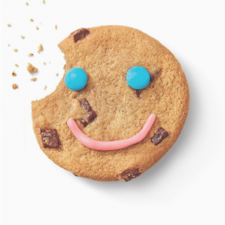 Cookie with a smile in icing with a bite out of it.